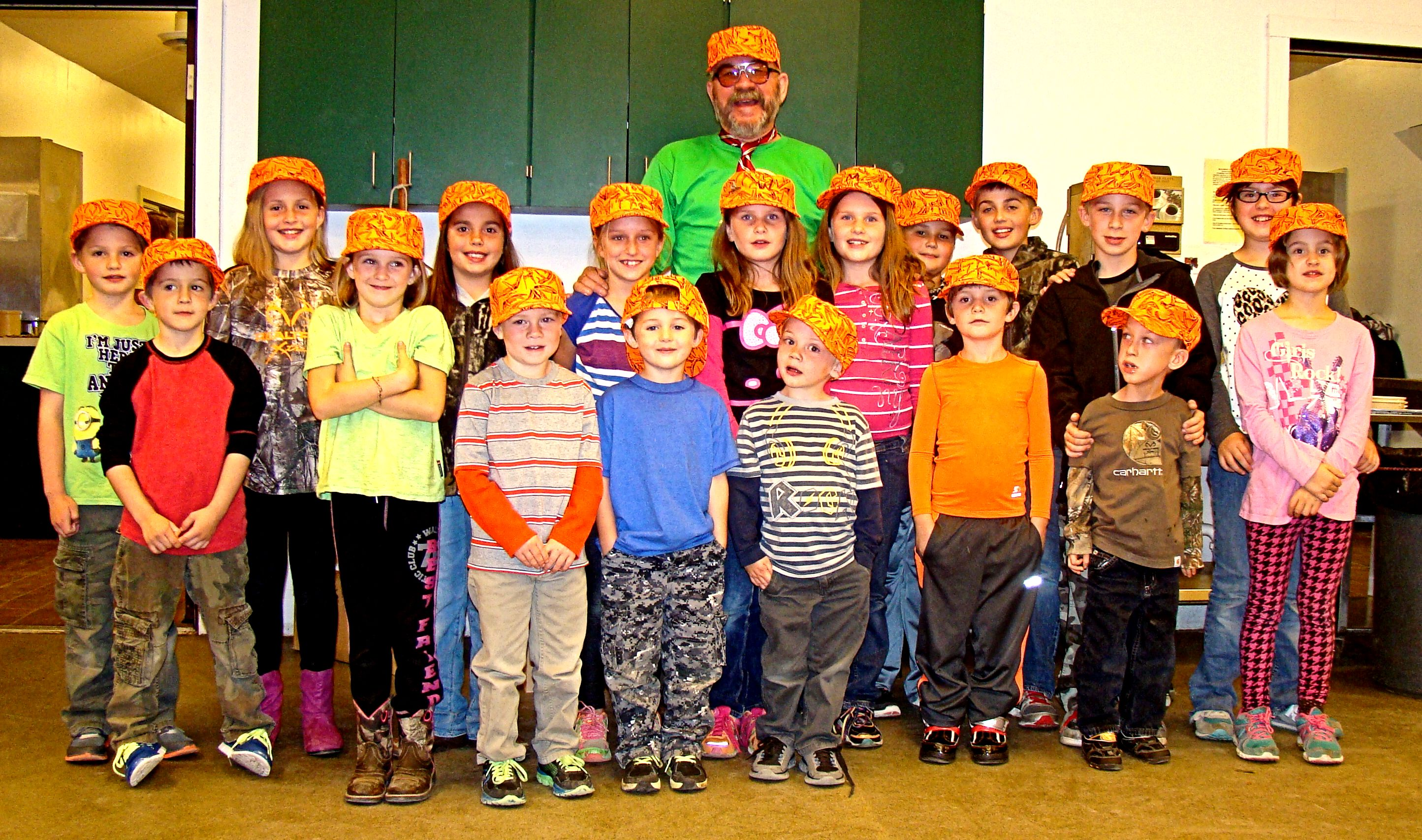 "Here is one good looking bunch or the ""Little People"" who attended this year's UFFDA Hunt wearing their special UFFDA hats and surrounding the biggest kid at the hunt."